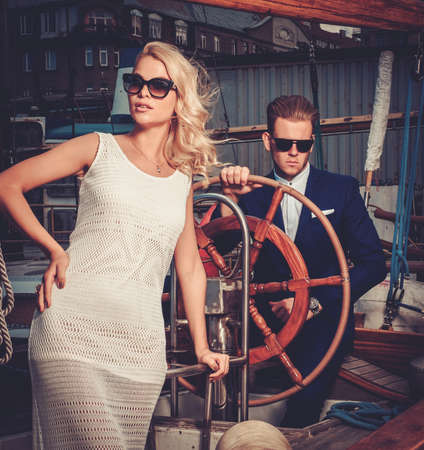 wealthy lifestyle: Stylish wealthy couple on a luxury yacht