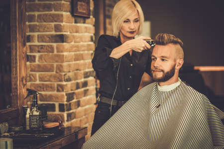 barber: Client visiting hairstylist in barber shop Stock Photo