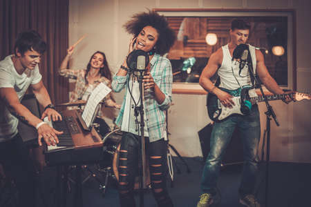 synthesiser: Multiracial music band performing in a recording studio