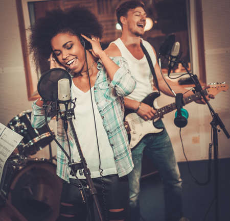 personas cantando: Banda de música multirracial realizar en un estudio de grabación