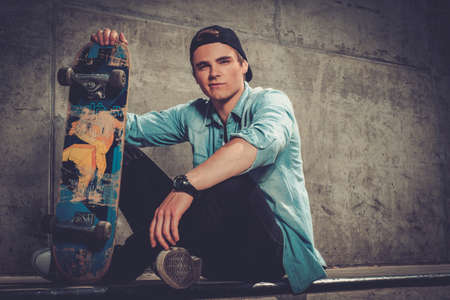 Handsome young man with skateboard outdoors