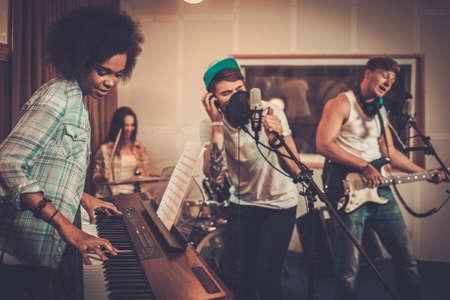 teclado: Banda de música multirracial realizar en un estudio de grabación
