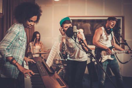 keyboard instrument: Multiracial music band performing in a recording studio