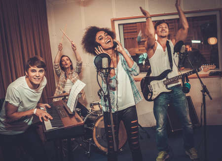 cantando: Banda de música multirracial realizar en un estudio de grabación