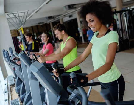eliptica: Gente que ejercita en la maquina de entrenamiento de cardio en un gimnasio