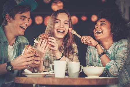 HAMBURGUESA: Amigos multirraciales alegre que come en un café Foto de archivo
