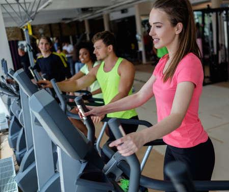 ejercicio aeróbico: Gente que ejercita en la maquina de entrenamiento de cardio en un gimnasio