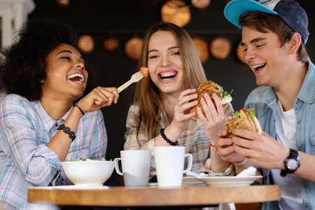 comiendo: Amigos multirraciales alegre que come en un caf� Foto de archivo
