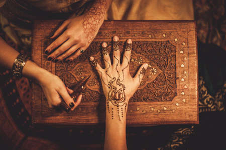 Ziehverfahren von Henna menhdi Ornament auf der Hand der Frau