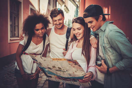 young black girl: Multiracial friends tourists with map in an old city