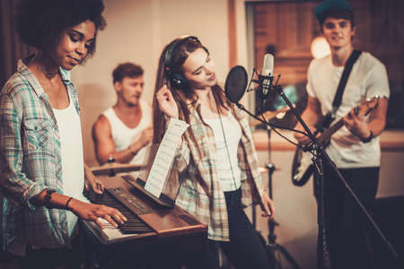 recordings: Multiracial music band performing in a recording studio