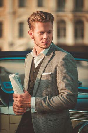 auto old: Joven rico confidente con el periódico cerca convertible clásico Foto de archivo