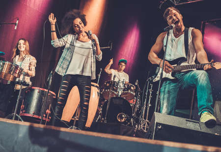 Multiracial music band performing on a stage Stock Photo