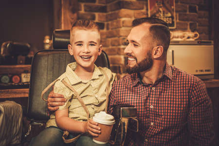 shave: Stylish little boy and his father in a barber shop