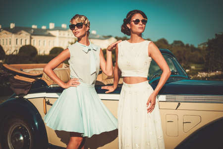 classic car: Two stylish ladies near classic convertible