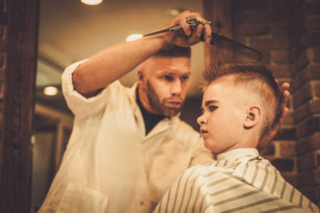 barber chair: Little boy visiting hairstylist in barber shop