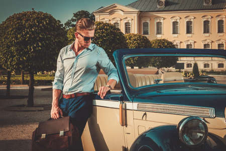 lifestyle: Joven rico confidente con maletín cerca convertible clásico