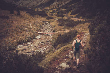 hiking stick: Woman with hiking poles walking in mountain landscape