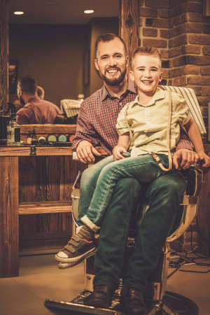 fathers: Stylish little boy and his father in a barber shop