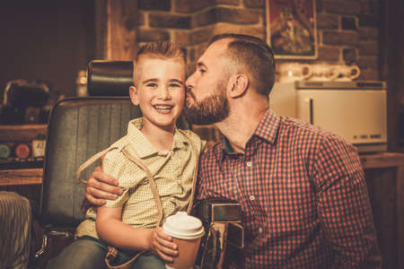 little boy: Stylish little boy and his father in a barber shop