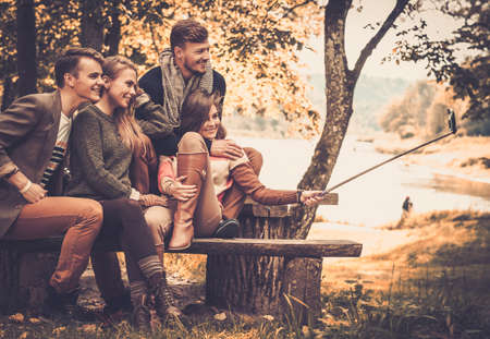 friends hugging: Cheerful friends in autumn park taking selfie Stock Photo