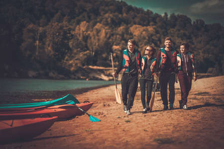 life jackets: Group of people wearing life jackets near kayaks on a beach Stock Photo