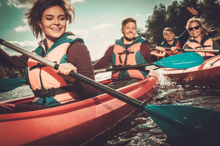 aventura: Grupo de gente feliz en un kayak Foto de archivo