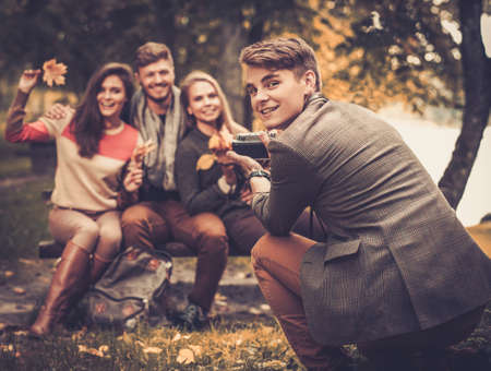 autumn in the park: Cheerful friends in autumn park taking picture
