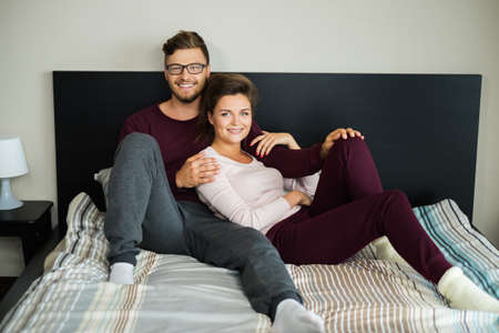 sofa bed: Cheerful couple on a bed at home
