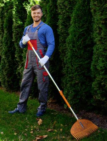 uniformes: Jardinero rastrillar las hojas Foto de archivo