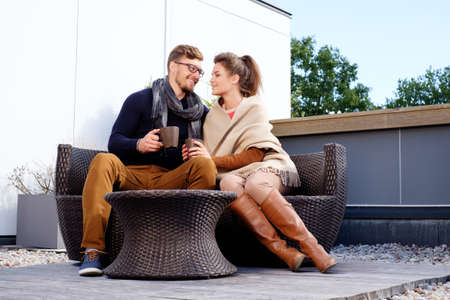 resting: Cheerful couple on a terrace on autumn day Stock Photo