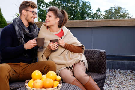 couple on couch: Cheerful couple on a terrace on autumn day Stock Photo