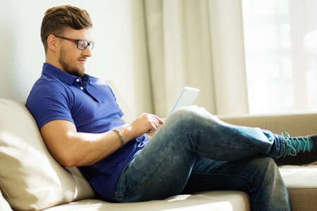 personas leyendo: Handsome man using tablet pc at home
