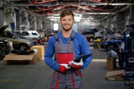 auto lift: Cheerful serviceman in a car workshop Stock Photo