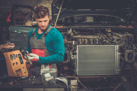 radiador: Mecánico con herramienta neumática en un taller