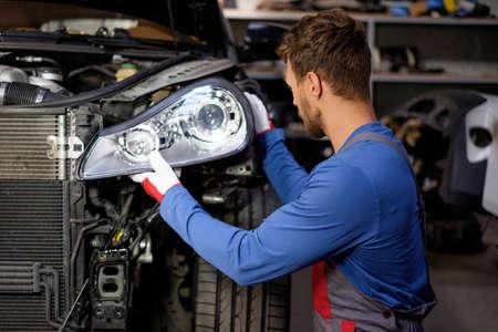Mécanicien avec le nouveau phare de voiture dans un atelier