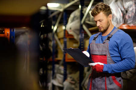 hombres trabajando: Trabajador en un almacén de piezas de repuesto automotriz