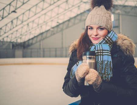 iceskates: Girl with mug of hot drink on ice skating rink