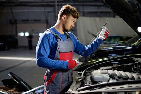garage automobile: M�canicien v�rifier le niveau d'huile dans un atelier de voiture