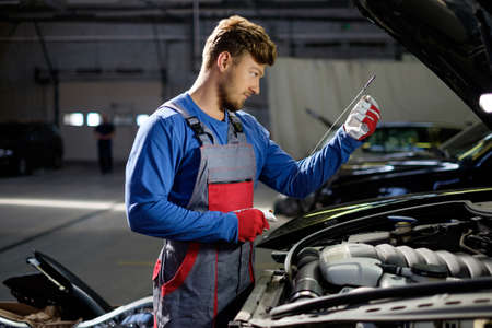 automobile workshop: Mechanic checking oil level in a car workshop Stock Photo