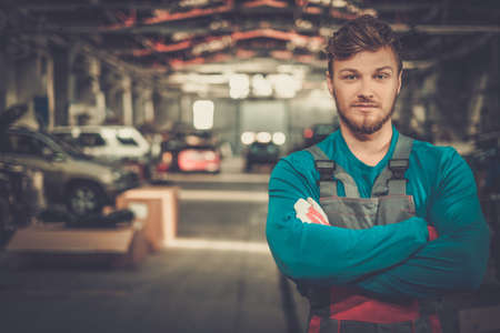 Técnico de servicio alegre en un taller de coches Foto de archivo