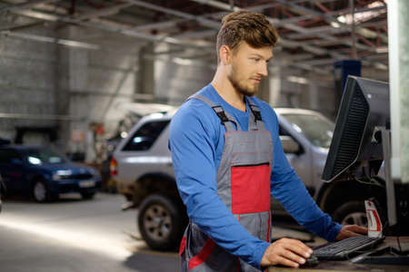 automobile workshop: Specialist near car diagnostic pc in a workshop Stock Photo