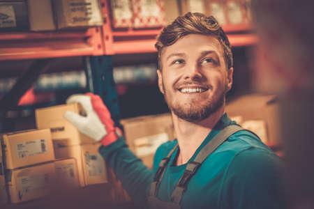 obrero trabajando: Trabajador en un almacén de piezas de repuesto automotriz