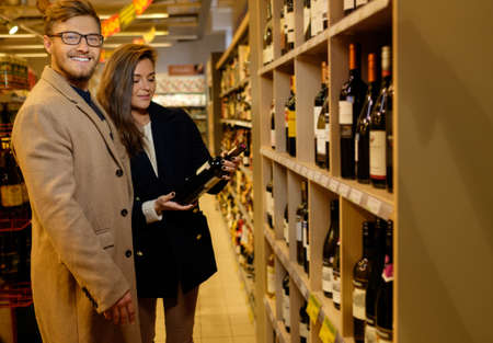 liquors: Couple choosing alcohol in a liquor store