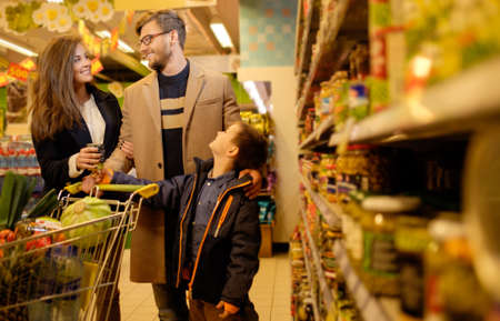 family budget: Young family in a grocery store Stock Photo