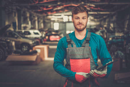 mechanic: Cheerful serviceman in a car workshop Stock Photo