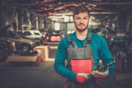 mecanico automotriz: Técnico de servicio alegre en un taller de coches Foto de archivo