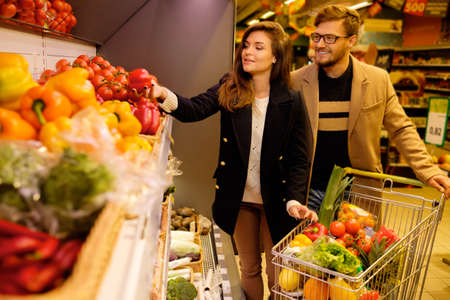 healthy economy: Couple choosing vegetables in a grocery store Stock Photo