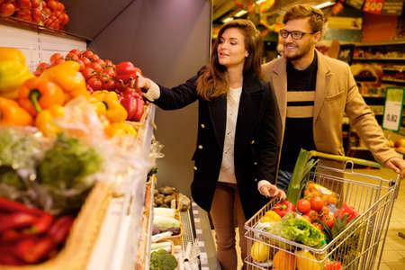 abarrotes: Pareja elegir verduras en un supermercado Foto de archivo