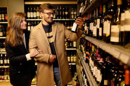 botella de licor: Pareja elegir alcohol en una tienda de licores
